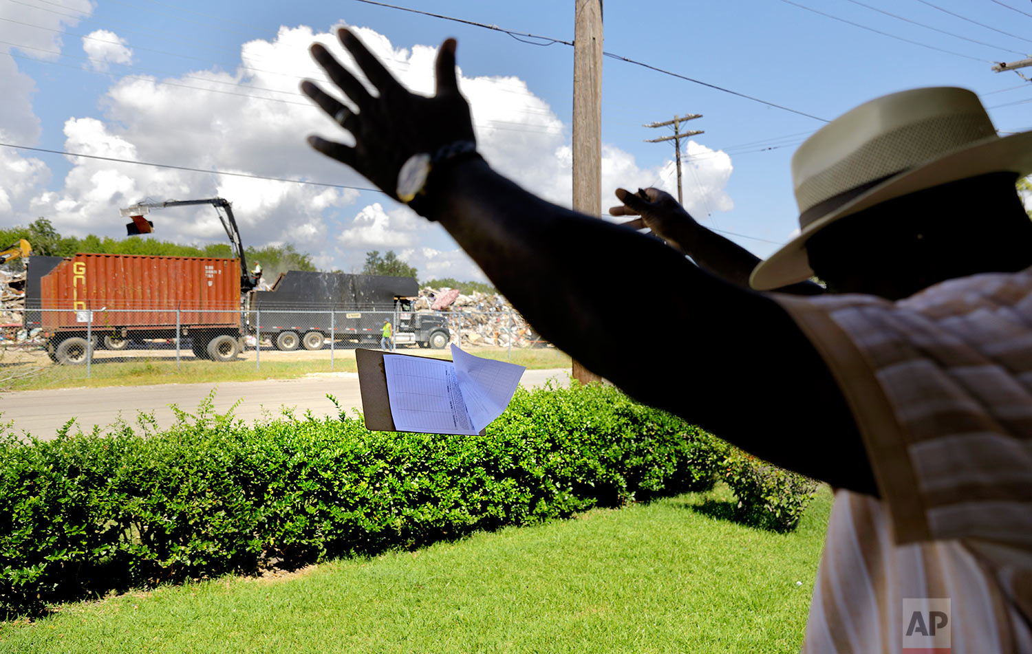 """Hilton Kelley tosses his petition clipboard in frustration as he's turned away from a renter who was told by her landlord not to get involved in Kelley's attempt to shutdown the dump across the street piled with flood damaged debris in Port Arthur, Texas, Wednesday, Sept. 27, 2017. """"This is an outrage. This is appalling. There's no way this should have happened,"""" said Kelly of the dump's proximity to people's homes. He worried about mold and other contaminants from the garbage getting into the low-income African American neighborhood. These are the neighborhoods, he said, that often pay the price for environmental pollution. Many of these neighborhoods also flooded. (AP Photo/David Goldman)"""