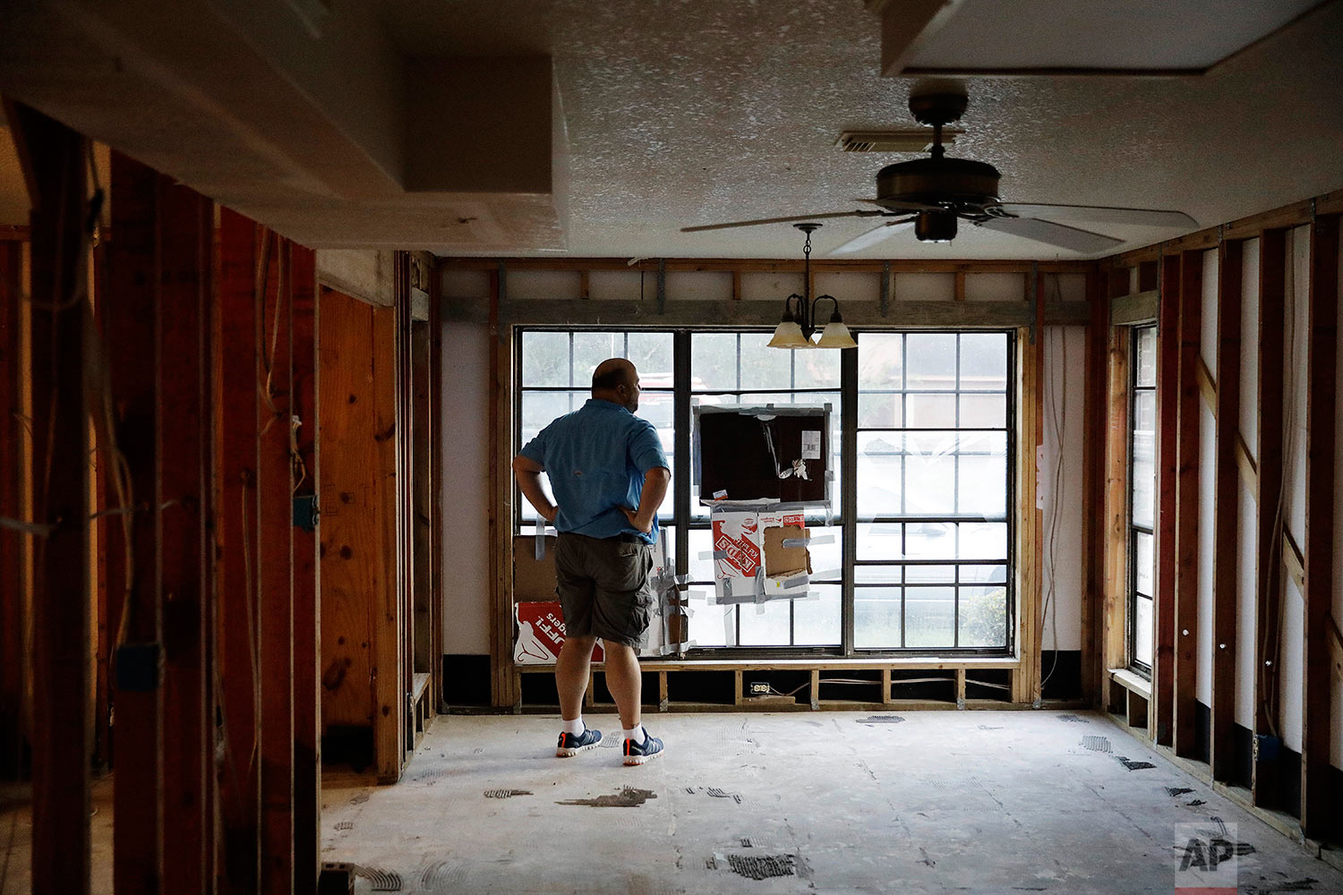 """Wilton Johnson stands in the gutted home in Beaumont, Texas, Monday, Sept. 25, 2017, that he shares with his parents. It was damaged by Hurricane Harvey. """"We need to be responsible human beings to the earth. But at the same time we shouldn't sacrifice the financial freedoms, the free market and free enterprise in a capitalistic society,"""" said Johnson, who supports Trump's environmental agenda. (AP Photo/David Goldman)"""