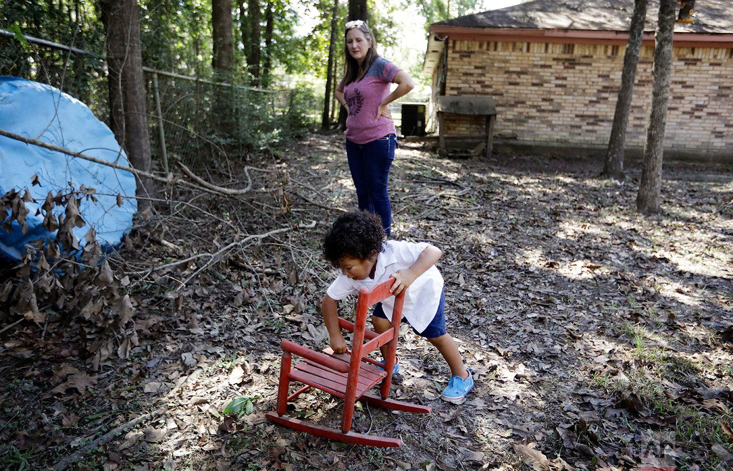Angela Lopez, watches as her grandson, Carter Gale, 2, cleans dirt off his chair in Beaumont, Texas, Tuesday, Sept. 26, 2017. He found it in the backyard, carried by water from inside their home during Hurricane Harvey flooding. Most of her family, including her husband, are conservatives, and have followed Trump's lead and dismiss the threat of climate change. Lopez worries this will keep happening until the nation is able to have a frank conversation about it. (AP Photo/David Goldman)