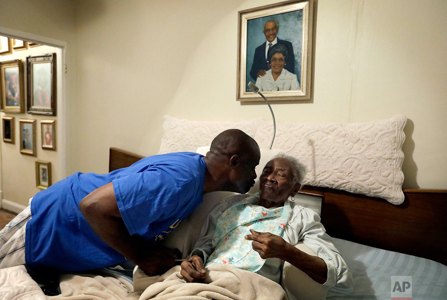 """Greg Gunner, left, kisses his grandmother Mabel Bishop, 99, on Tuesday, Sept. 26, 2017 in Port Arthur, Texas, in their home that was damaged by Hurricane Harvey. Gunner carried his grandmother, stricken with Alzheimer's disease, out of the house as the floodwaters rose, telling her they were going fishing to try to keep her calm. He voted for Hillary Clinton in November, and says the country's political divides have left him with little faith in the government's ability to get things done. But he believes the storm that wrecked his town is a preview of what global warming will bring if the nation's divided political sides don't find common ground to address it. """"The intensity of the destruction taking place these days, there's something going on. I think it's a wake-up call, to say, hey, what's important? What's really important?"""" he said. """"Are you going to work together, or are you going to pull each other apart?"""" (AP Photo/David Goldman)"""