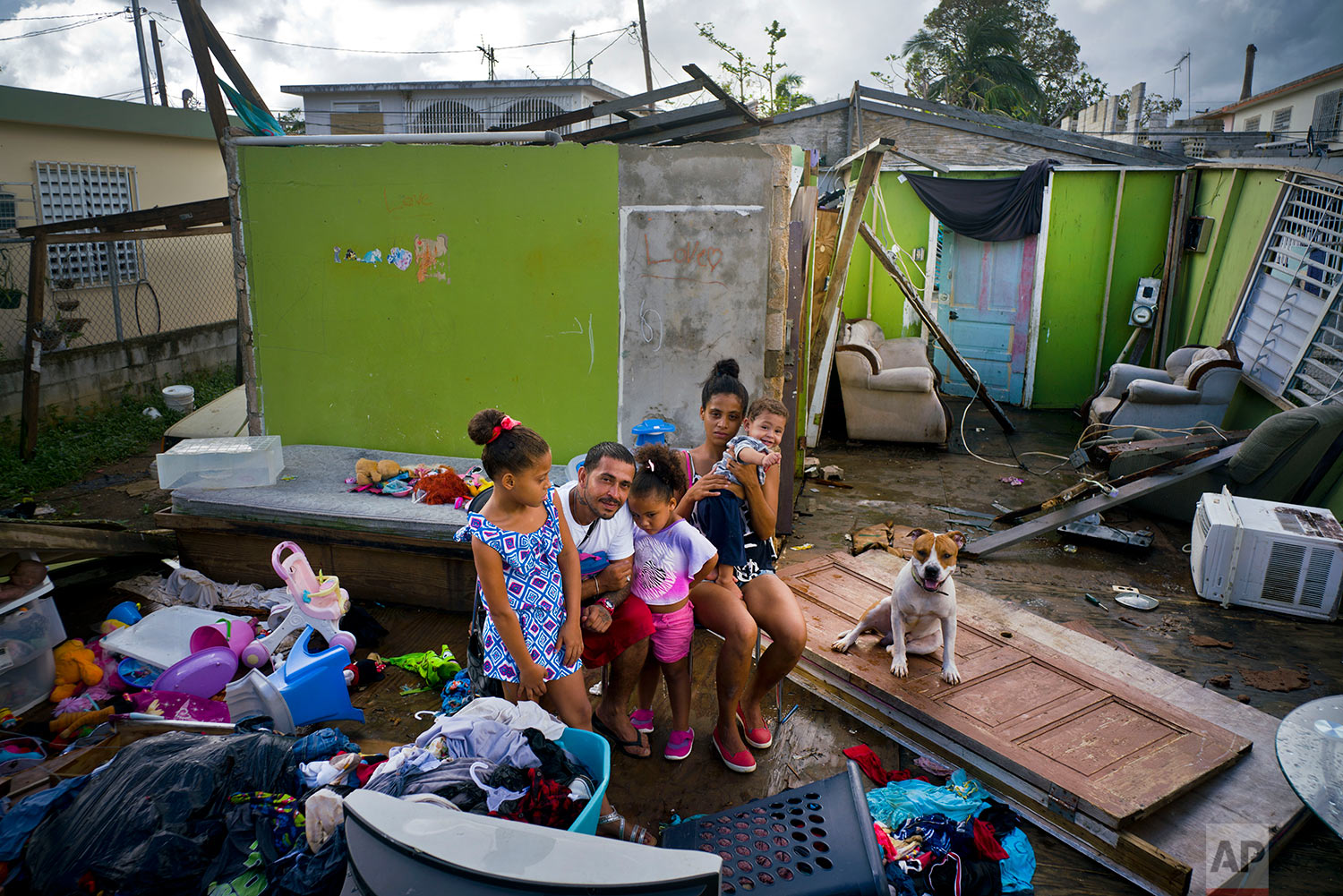 In this Saturday, Oct. 14, 2017 photo, Arden Dragoni, second from left, poses with his wife Sindy, their three children and dog Max, surrounded by what remains of their home destroyed by Hurricane Maria in Toa Baja, Puerto Rico. (AP Photo/Ramon Espinosa)