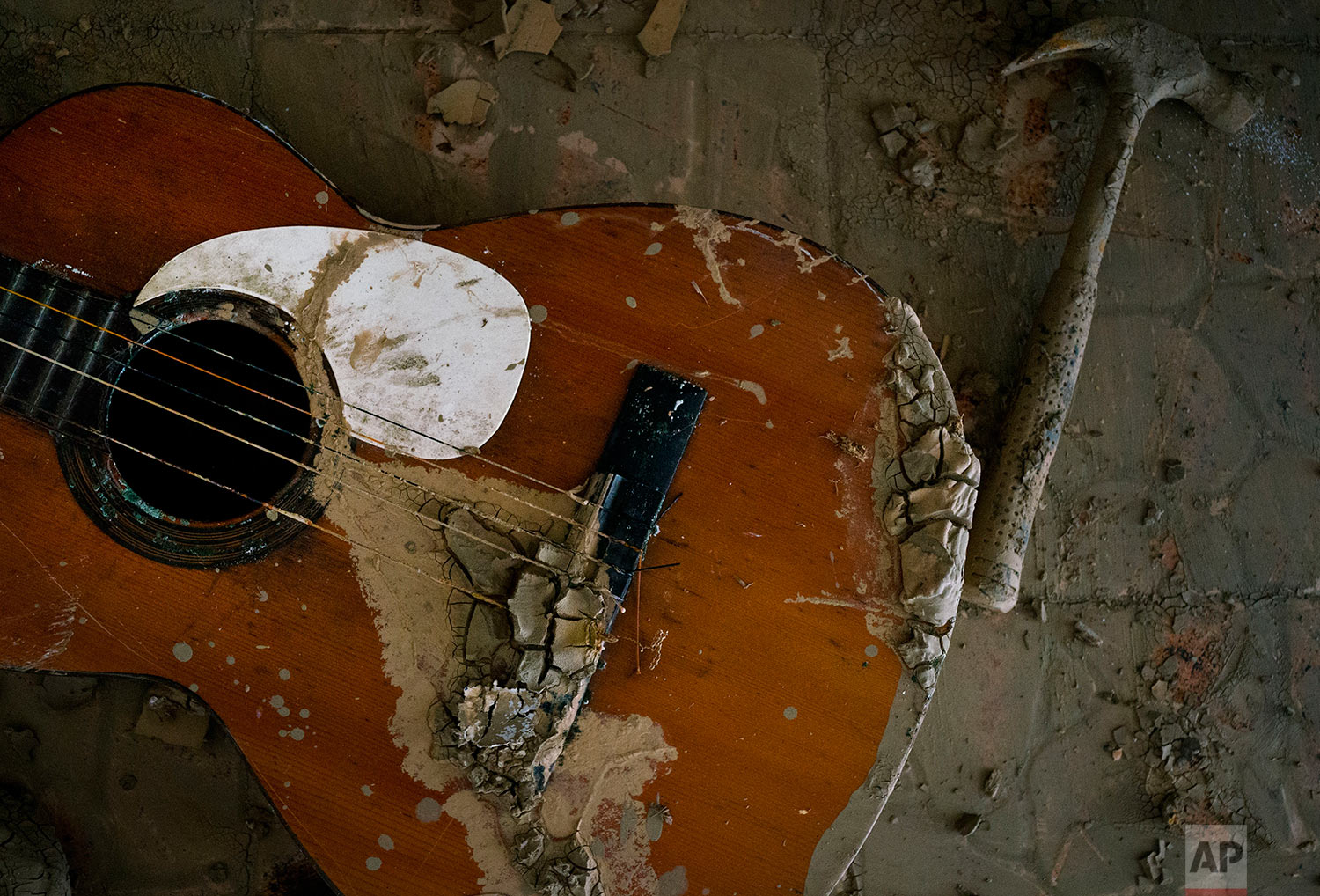 In this Friday, Oct. 13, 2017 photo, a destroyed guitar lays amid the mud and rubble of what's left of Jose Soto's home in Toa Baja, Puerto Rico.  (AP Photo/Ramon Espinosa)