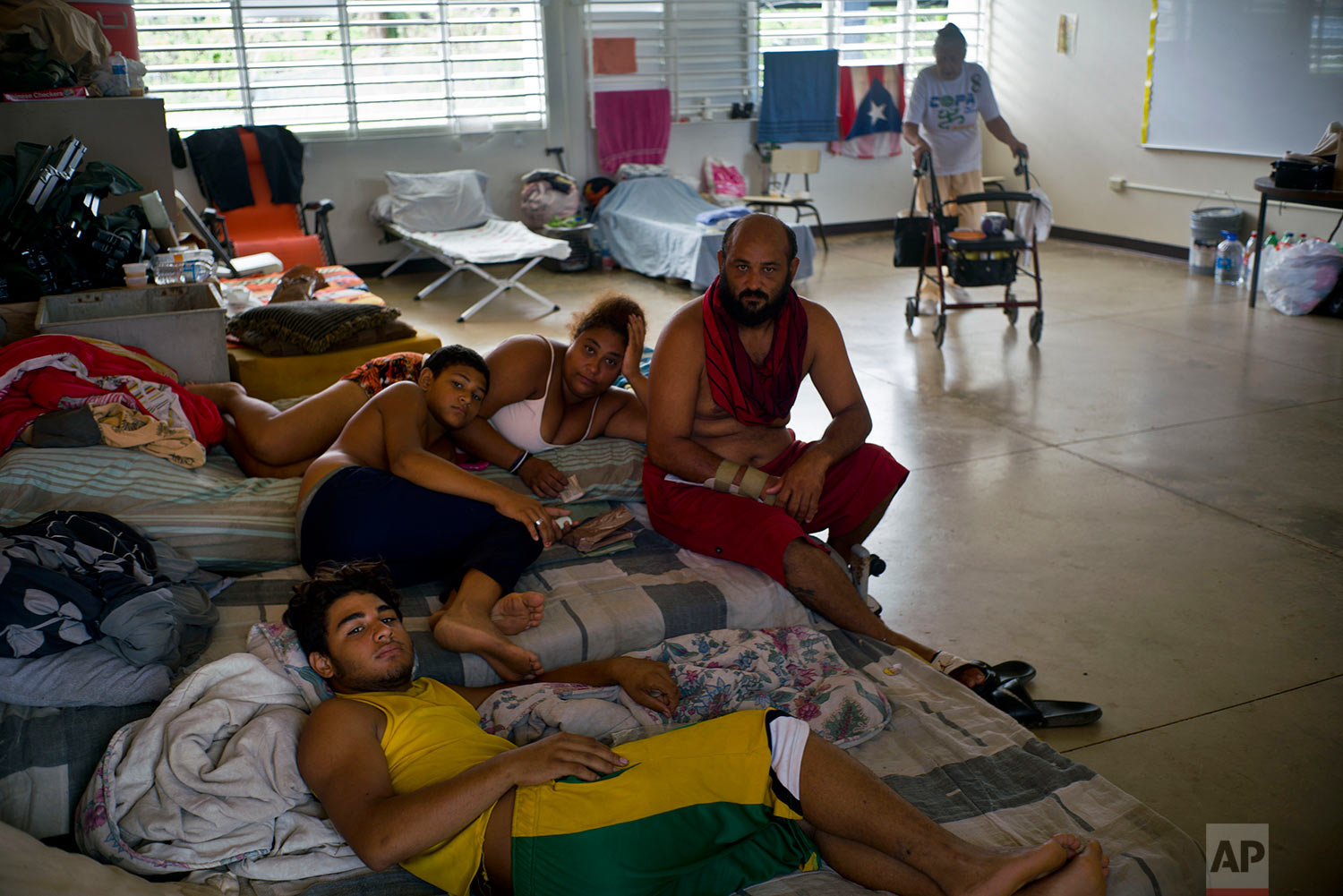 In this Saturday, Oct. 14, 2017 photo, Arturo de Jesus Melendez, center, sits with his wife Madeli and their children Alexis and Arturo on their mattresses inside a classroom at a school-turned-shelter after they were left homeless by Hurricane Maria in Toa Baja, Puerto Rico. (AP Photo/Ramon Espinosa)