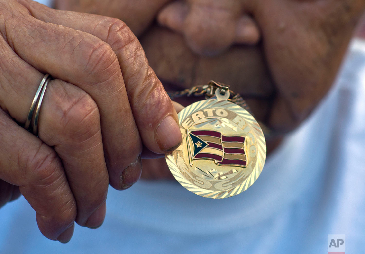 In this Thursday, Oct. 12, 2017 photo, Agustina Lugo Solis shows her necklace pendent decorated with a Puerto Rican flag, as she lives in a school-turned-shelter after her home was destroyed by Hurricane Maria in Toa Baja, Puerto Rico.  (AP Photo/Ramon Espinosa)