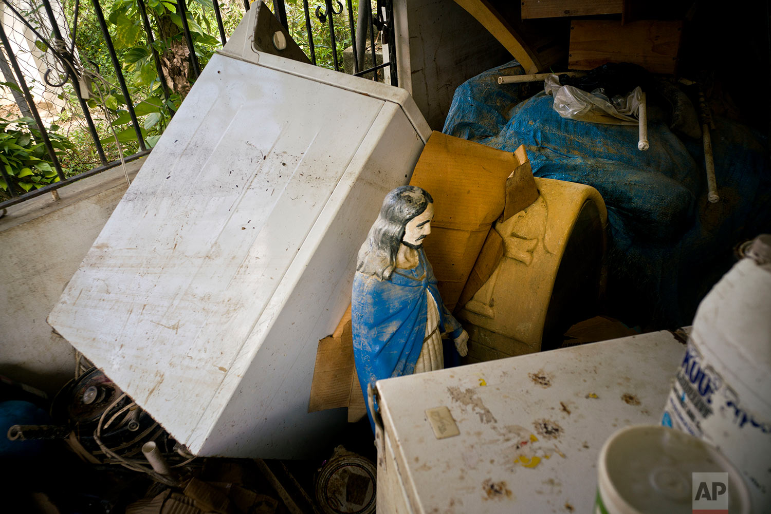 In this Friday, Oct. 13, 2017 photo, a statue of Jesus Christ stands amid what's left inside a home that was flooded by Hurricane Maria in Toa Baja, Puerto Rico. (AP Photo/Ramon Espinosa)