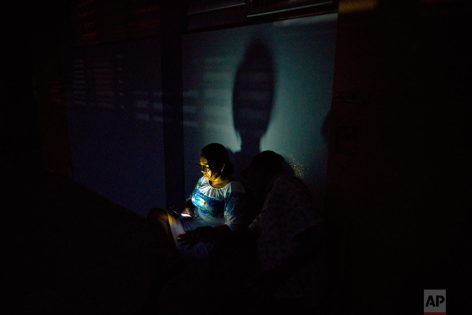 In this Thursday, Oct. 12, 2017 photo, a woman left homeless by Hurricane Maria uses her cell phone at a school-turned-shelter that does not have electricity in Toa Baja, Puerto Rico. (AP Photo/Ramon Espinosa)