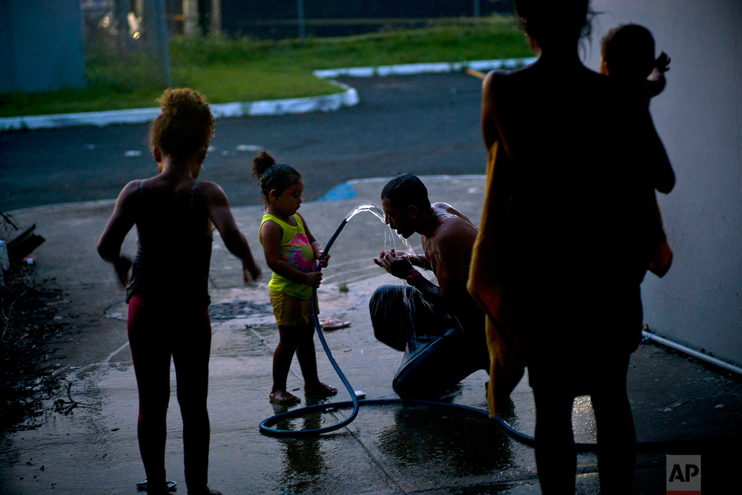 In this Thursday, Oct. 12, 2017 photo, Ander Dragoni showers with the help of his daughter holding the water hose, as they live at a school serving as a shelter for families left homeless by Hurricane Maria in Toa Baja, Puerto Rico.  (AP Photo/Ramon Espinosa)