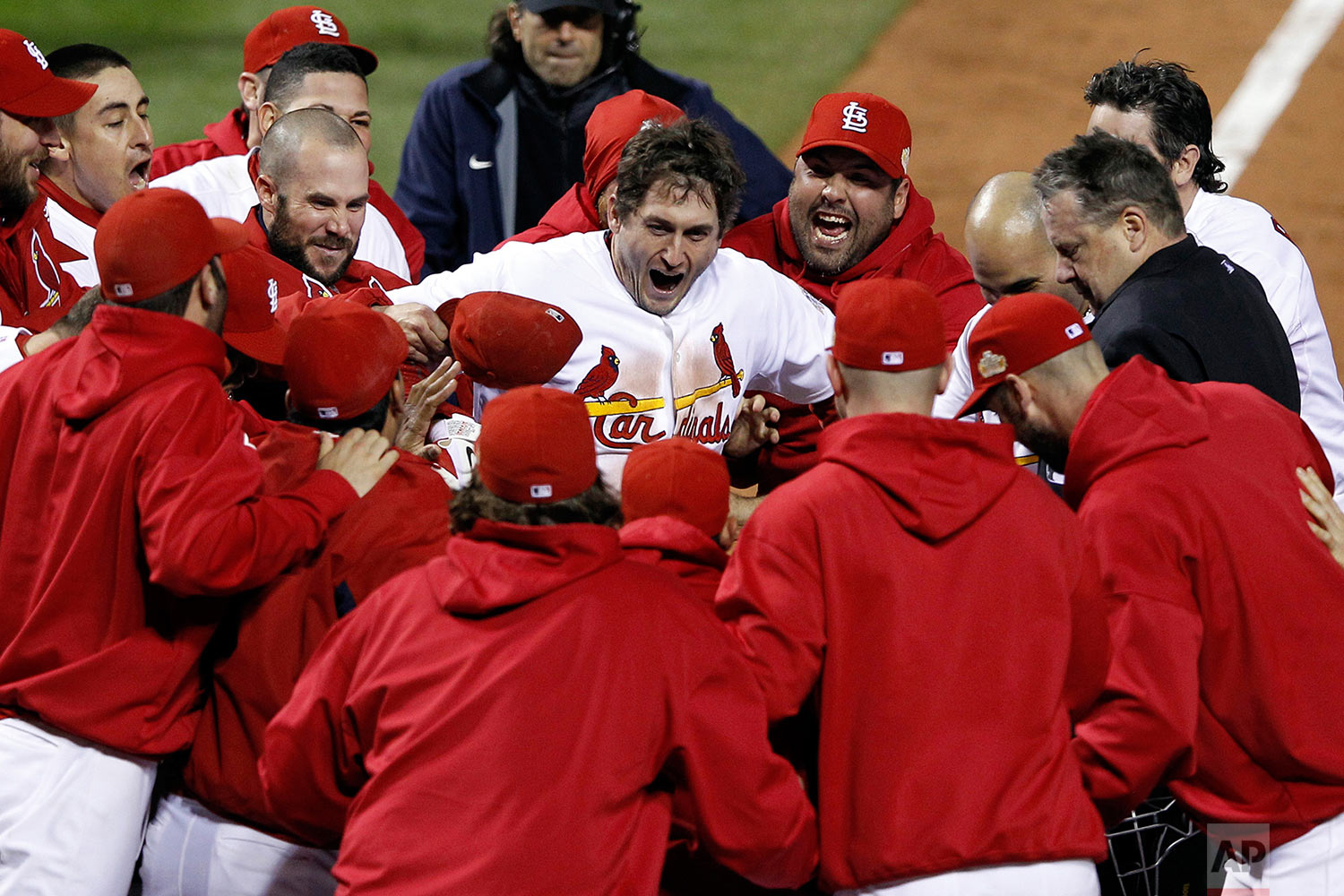 In this Oct. 27, 2011 photo, St. Louis Cardinals' David Freese, center, celebrates with teammates after hitting a walk-off home run in the 11th inning of Game 6 of baseball's World Series against the Texas Rangers in St. Louis. (AP Photo/Eric Gay)