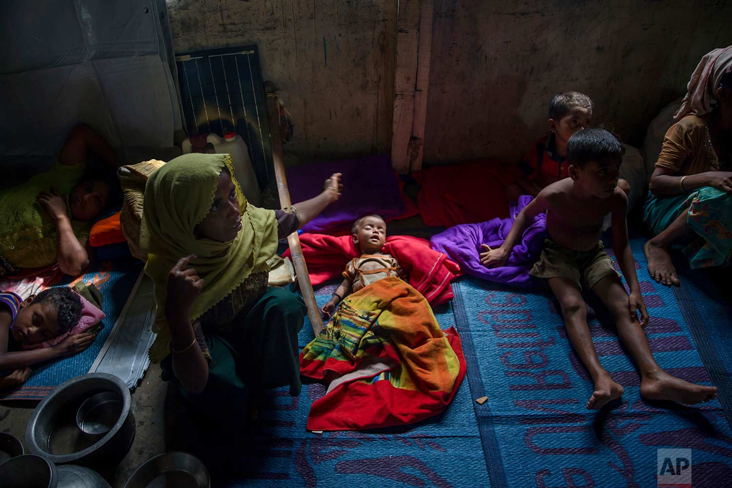A Rohingya Muslim woman keeps flies away from her sick daughter as she waits inside a classroom of a school to be registered which will then allow them to proceed to build a shelter in Kutupalong refugee camp, Bangladesh, Friday, Oct. 20, 2017. (AP Photo/Dar Yasin)