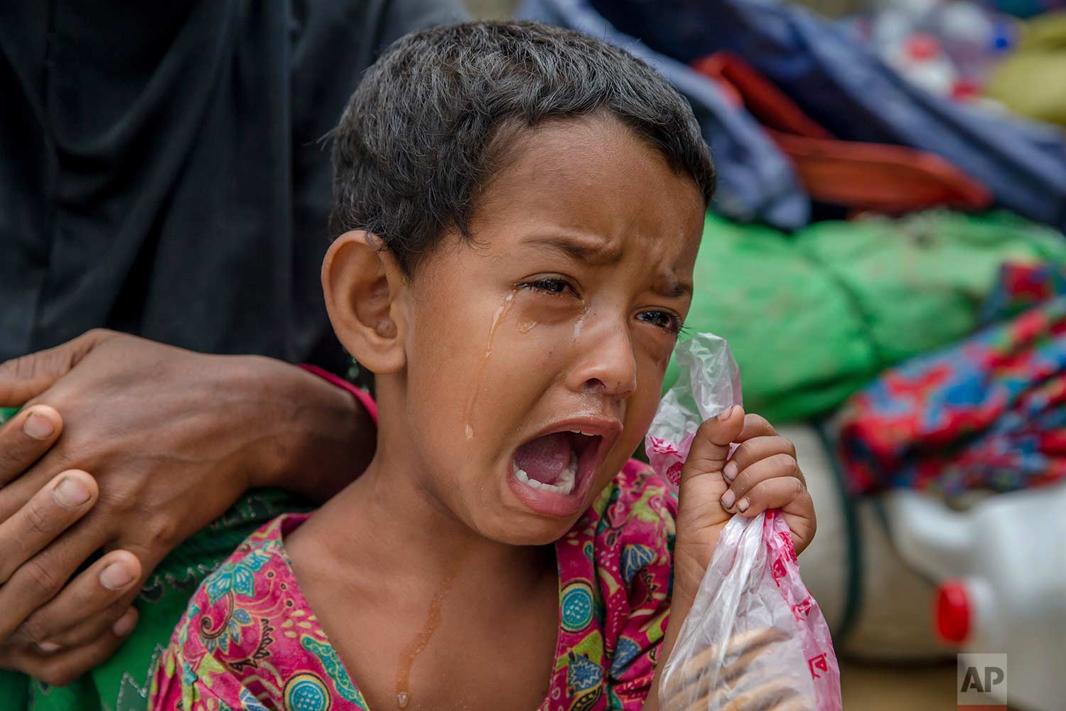 A Rohingya Muslim girl Toyiba Khatun cries while fighting fever as she waits with her family to be registered which will then allow them to proceed to build a shelter in Kutupalong refugee camp, Bangladesh, Friday, Oct. 20, 2017. (AP Photo/Dar Yasin)