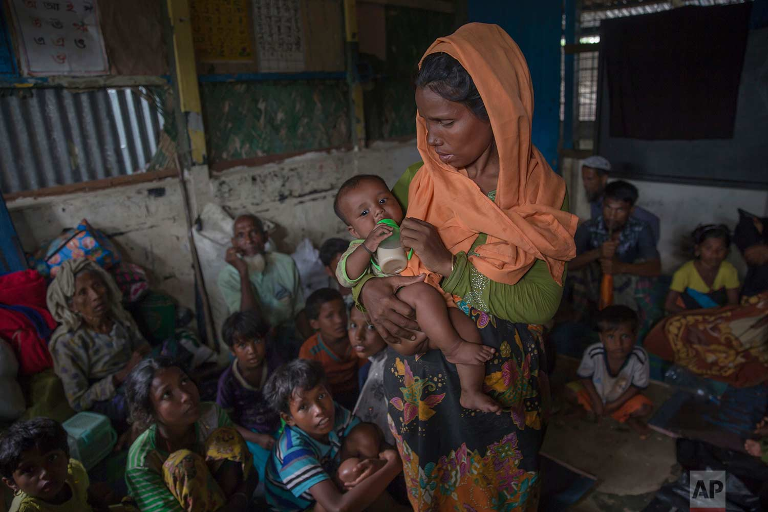 A Rohingya Muslim woman feeds her daughter inside a classroom where a group of refugees wait to be registered after which they will be allowed to proceed to build a shelter in Kutupalong refugee camp, Bangladesh, Friday, Oct. 20, 2017. (AP Photo/Dar Yasin)