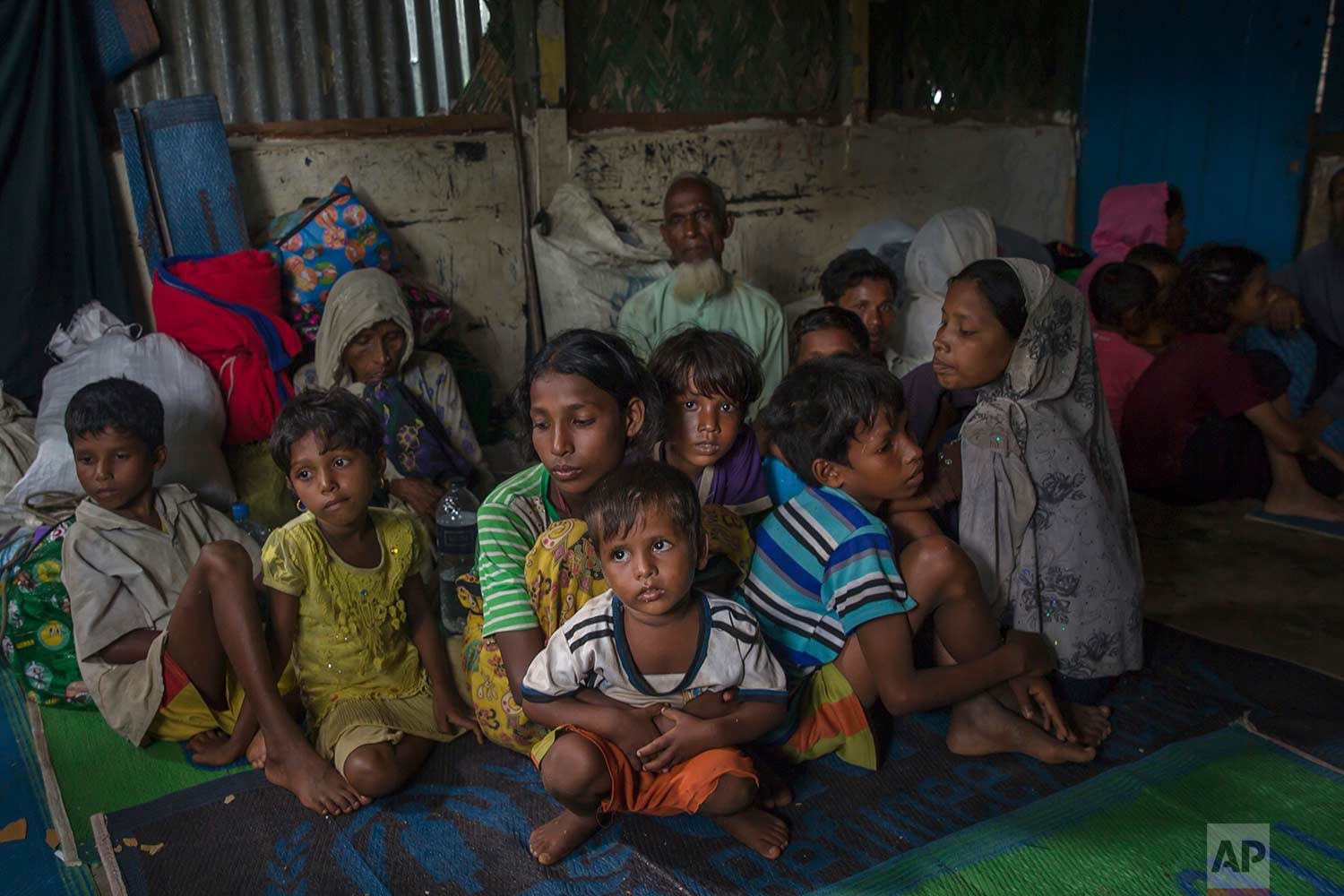 Rohingya Muslims sit inside a classroom waiting to be registered after which they will be allowed to proceed to build a shelter in Kutupalong refugee camp, Bangladesh, Friday, Oct. 20, 2017. (AP Photo/Dar Yasin)