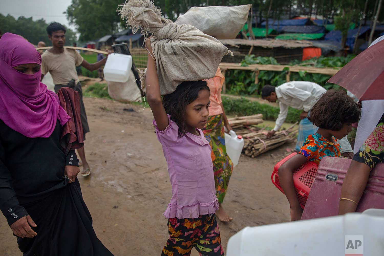 A newly arrived Rohingya Muslim girl, who crossed over from Myanmar into Bangladesh, walks carrying her belongings near Kutupalong refugee camp, Bangladesh, Friday, Oct. 20, 2017. (AP Photo/Dar Yasin)