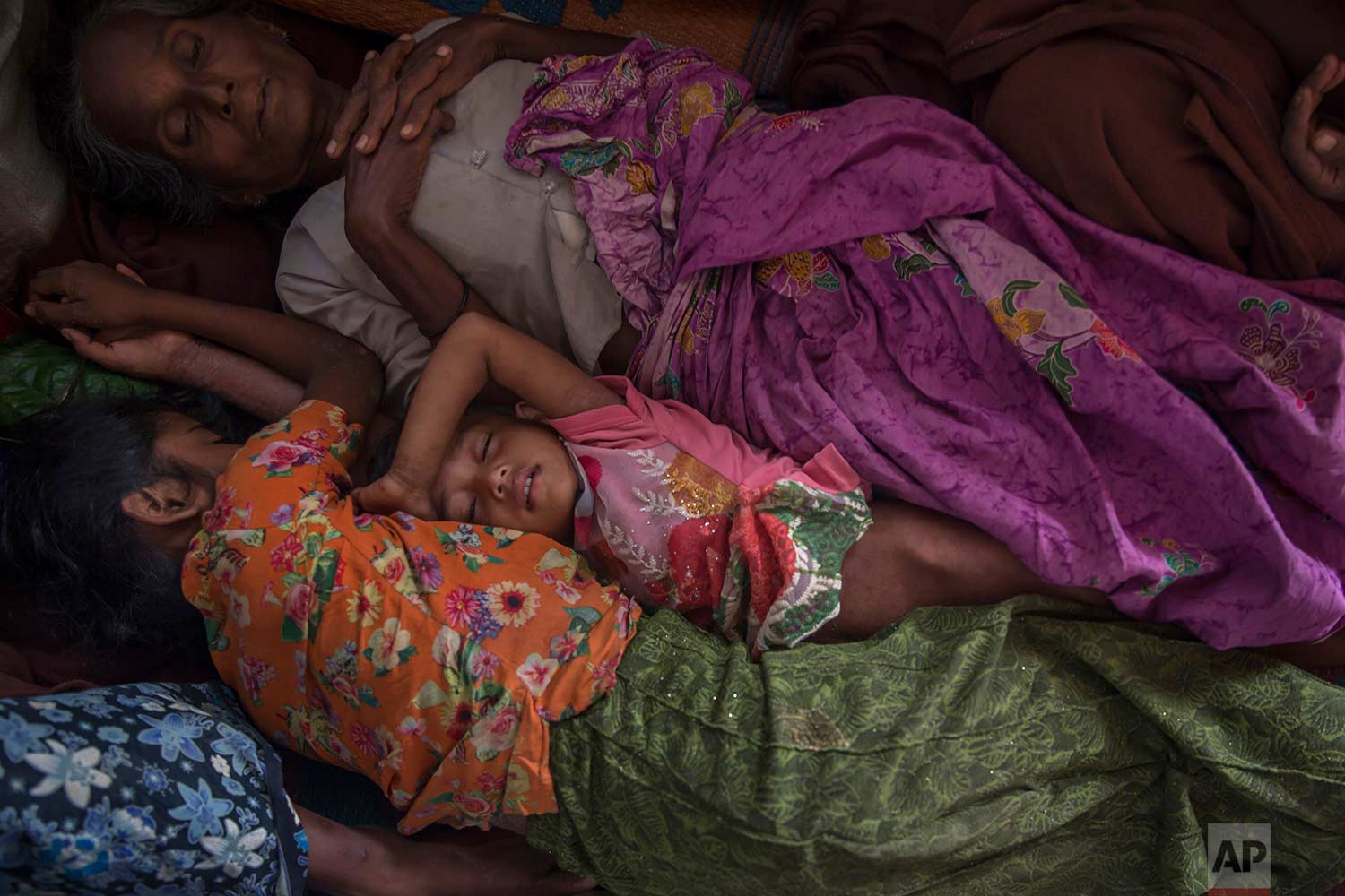 A Rohingya Muslim girl Asma Bibi, center, sleeps between her grandmother and sister in a dormitory of a school as they wait for their family to be registered as refugees after which they will be allowed to proceed to build a shelter in Kutupalong refugee camp, Bangladesh, Friday, Oct. 20, 2017.(AP Photo/Dar Yasin)