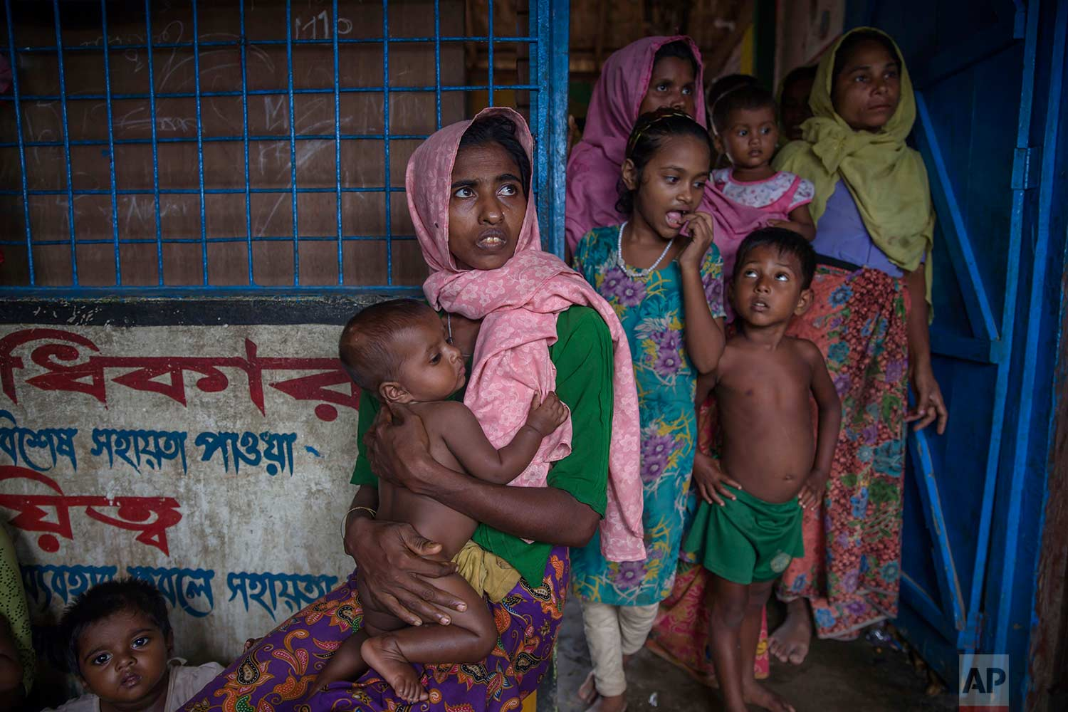 A Rohingya Muslim woman Nur Nahar, center, who crossed over from Myanmar into Bangladesh, holds her son Mohammad Junaid, as she sits in a dormitory of a school for her family to be registered as refugees after which they will be allowed to proceed to build a shelter in Kutupalong refugee camp, Bangladesh, Friday, Oct. 20, 2017. (AP Photo/Dar Yasin)
