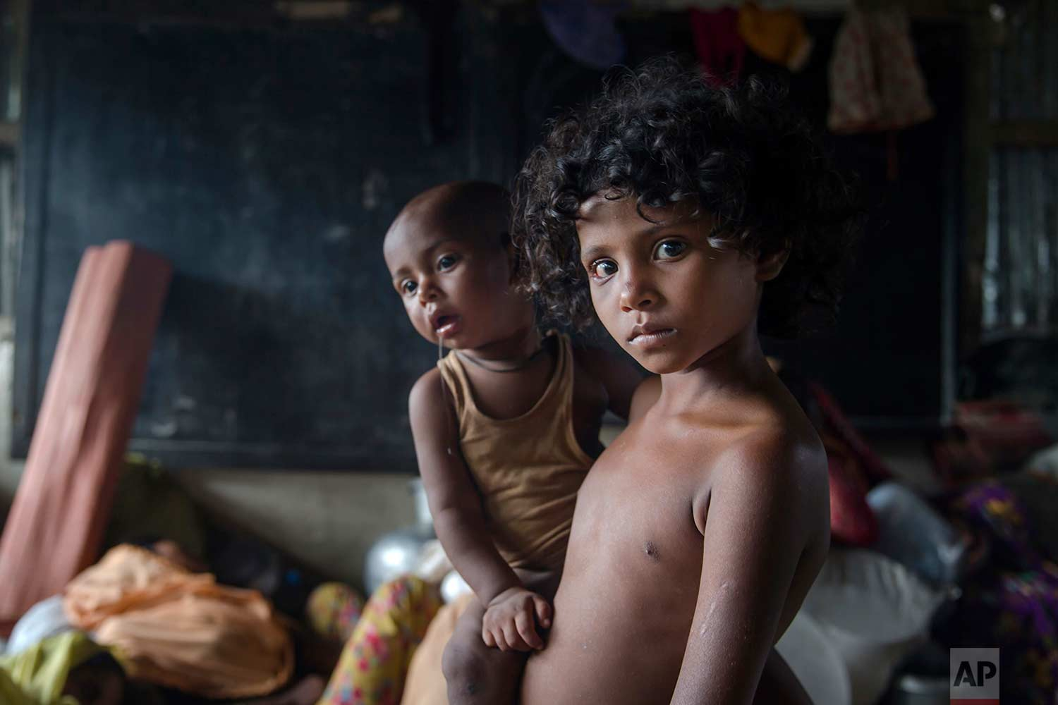 A Rohingya Muslim girl Azra, who crossed over from Myanmar into Bangladesh, holds her little brother Luqman and waits for their family to be registered as refugees after which they will be allowed to proceed to build a shelter in Kutupalong refugee camp, Bangladesh, Friday, Oct. 20, 2017.(AP Photo/Dar Yasin)