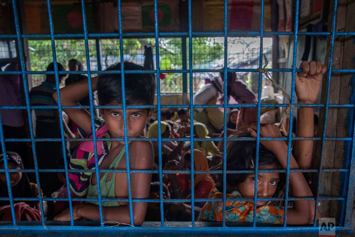 Rohingya Muslim children, who crossed over from Myanmar into Bangladesh, wait inside a classroom for their families to be registered as refugees after which they will be allowed to proceed to build a shelter in Kutupalong refugee camp, Bangladesh, Friday, Oct. 20, 2017. (AP Photo/Dar Yasin)