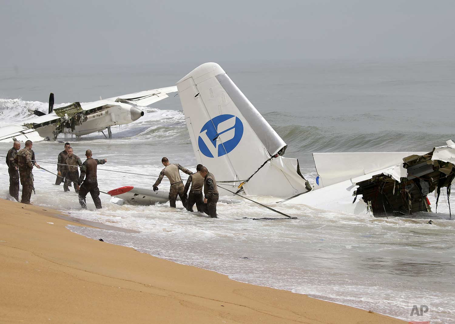 French troops try to pull parts of a cargo plane onto the shore in Abidjan, Ivory Coast on Saturday Oct. 14, 2017. (AP Photo/Diomande Ble Blonde)