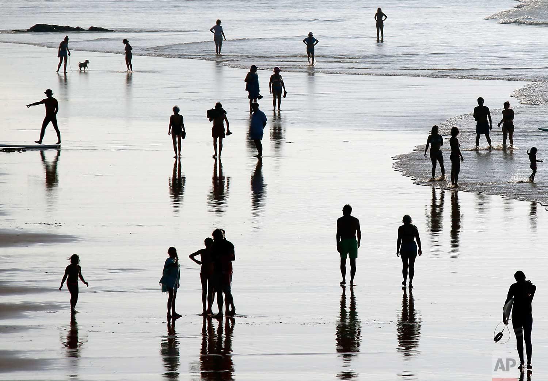 People walk on the beach in Biarritz, southwestern France, Saturday, Oct. 14, 2017. (AP Photo/Bob Edme)