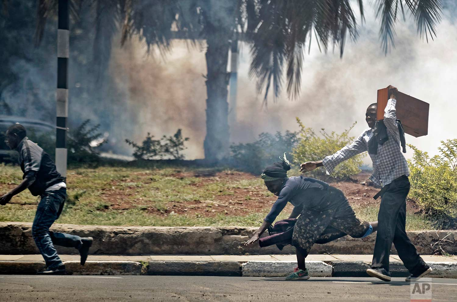 A passerby stumbles to the ground as she and opposition supporters, protesting over the upcoming elections, run for safety amid a cloud of tear gas fired by riot police in downtown Nairobi, Kenya, on Monday, Oct. 16, 2017. (AP Photo/Ben Curtis)