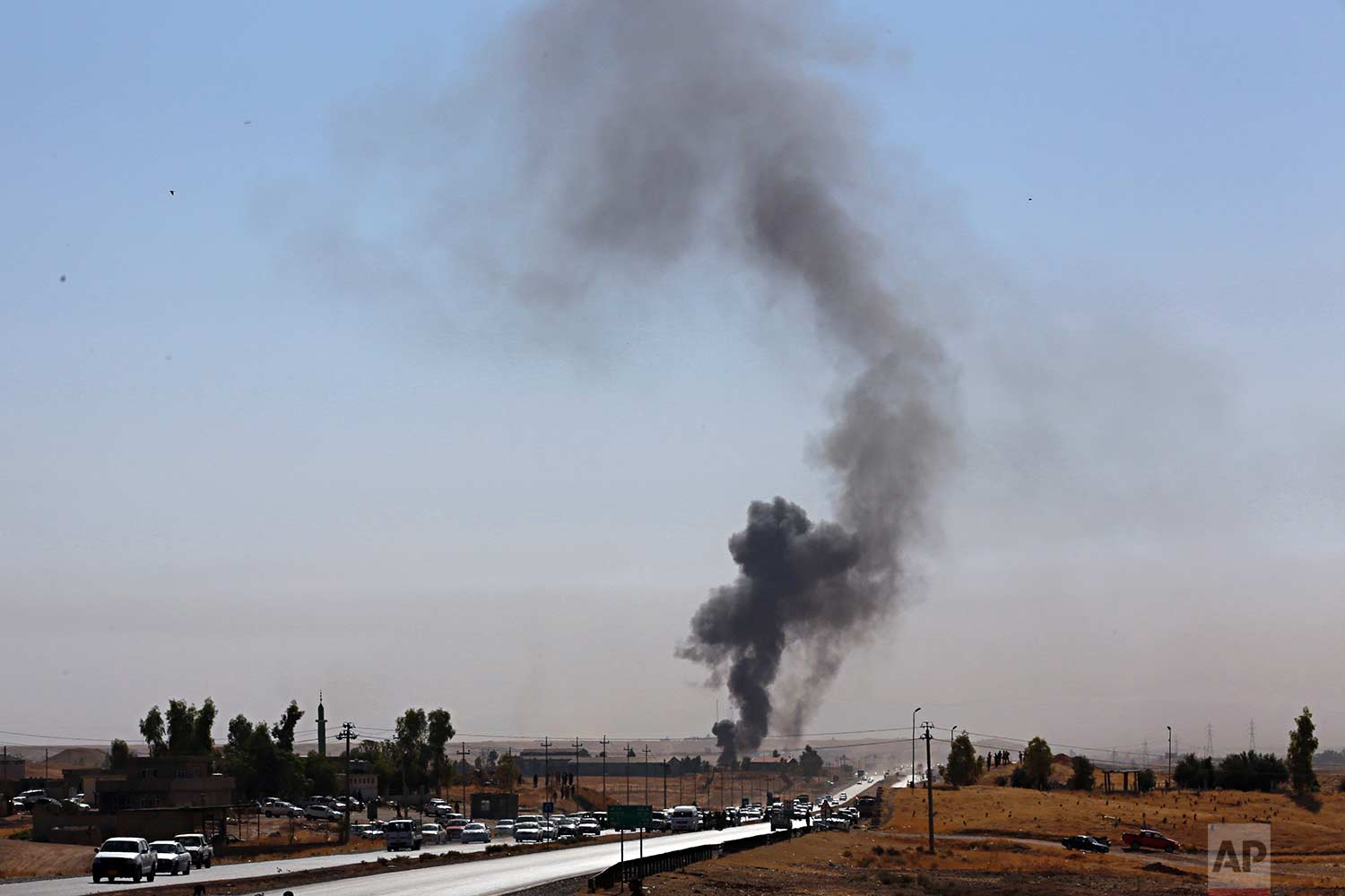 Smoke rises as Iraqi security forces launch explosives as Kurdish security forces withdraw from a checkpoint in Altun Kupri, on the outskirts of Irbil, Iraq, Friday Oct. 20, 2017. (AP Photo/Khalid Mohammed)