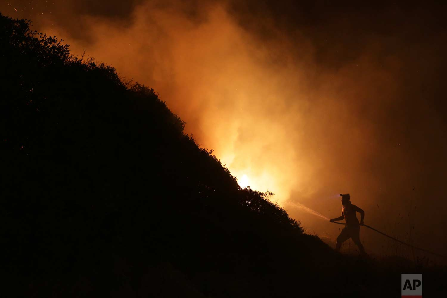 A volunteer uses a water hose to fight a wildfire near houses on the outskirts of Obidos, Portugal, in the early hours of Monday, Oct. 16, 2017. (AP Photo/Armando Franca)