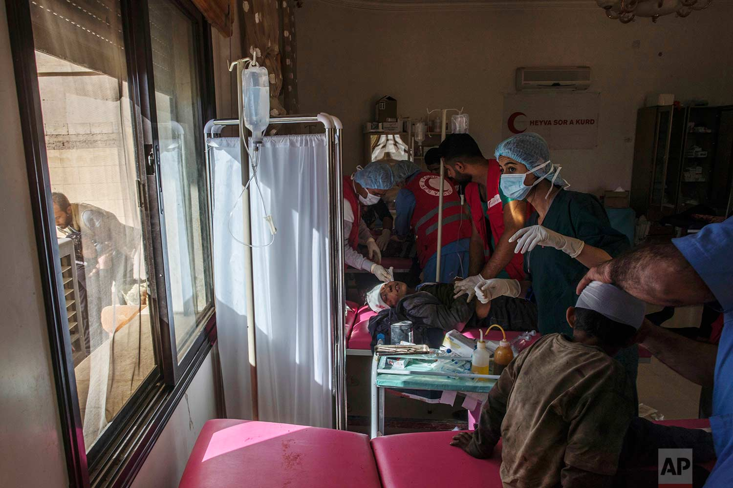 Red Crescent doctors treat three children injured in a motorcycle accident as a mother of one child weeps outside, in Raqqa, Syria, on Thursday, Oct. 19, 2017. (AP Photo/Gabriel Chaim)