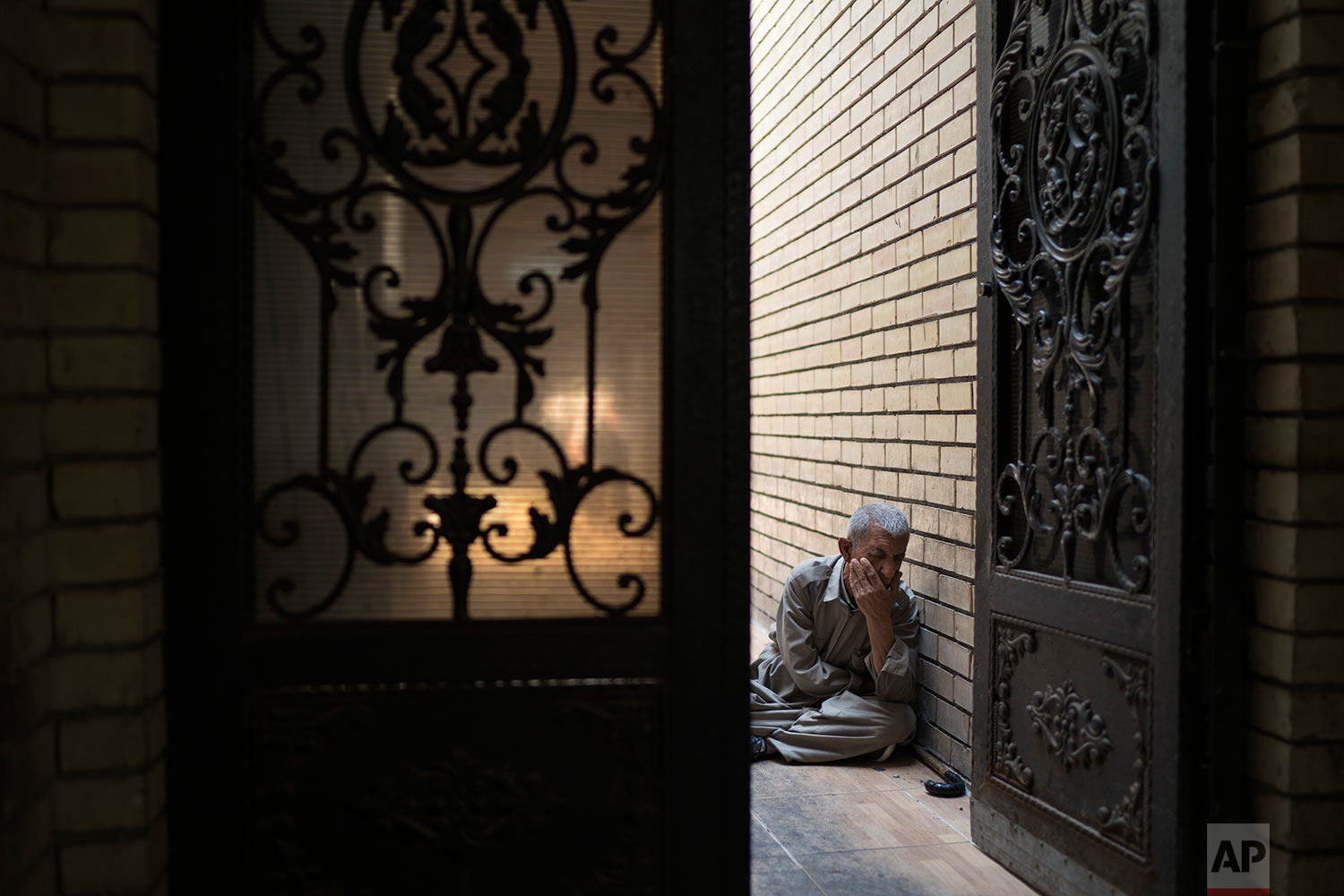 A man sits at the entrance of a mosque in central Irbil, Iraq, Wednesday, Oct. 25, 2017. In Sept. 2017, Iraq's Kurds celebrated their symbolic vote for independence, but instead of moving forward with negotiations toward a smooth divorce from Baghdad, they have lost their most important oil-producing city to Iraqi troops, squeezing a hurting economy and dashing the hopes of an independent state. (AP Photo/Felipe Dana)