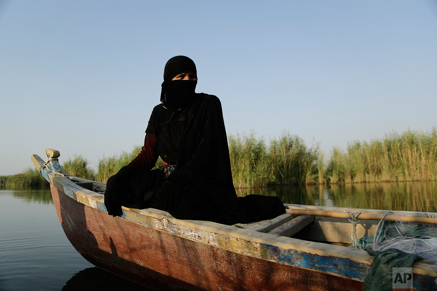 In this Sept. 11, 2017 photo, a fisherwoman prepares to lay out her netting beside a bank of reeds in the marsh of Chabaish, Iraq. The majority of the marsh's roughly 6,000 inhabitants subsist on fishing and raising water buffalo, but as water quality continues to drop, yields have diminished and increasingly residents are living in poverty. (AP Photo/Susannah George)