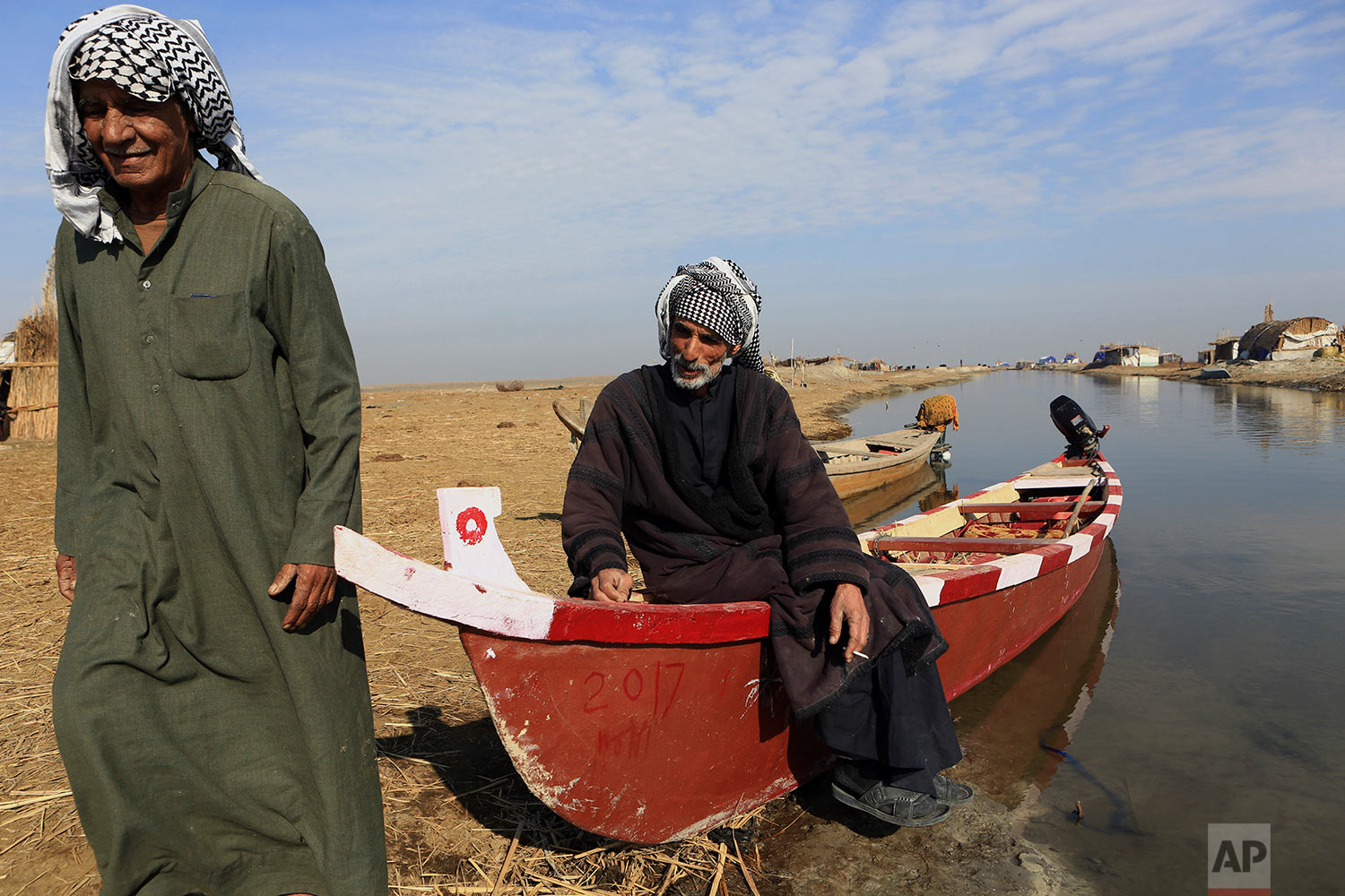 Boats owners are seen in the Chabaish marsh, in the Maysan province of southern Iraq, Saturday, Jan. 7, 2017. (AP Photo/Nabil al-Jurani)