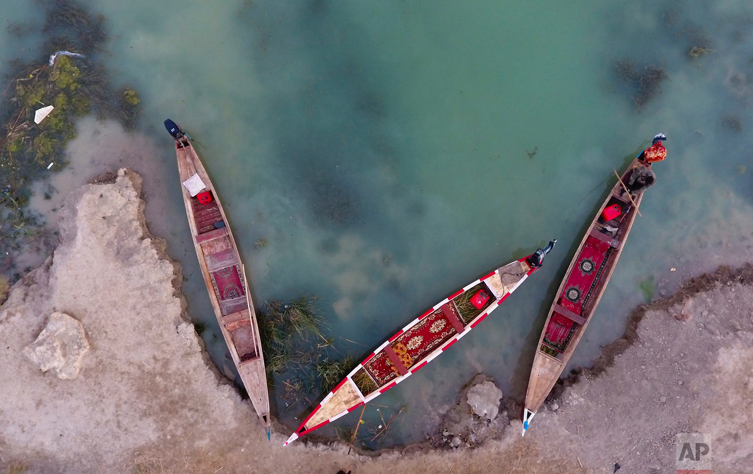 Boats owners are seen in the Chabaish marsh, in the Maysan province of southern Iraq, Saturday, Jan. 7, 2017. (AP Photo/ Nabil al-Jurani)