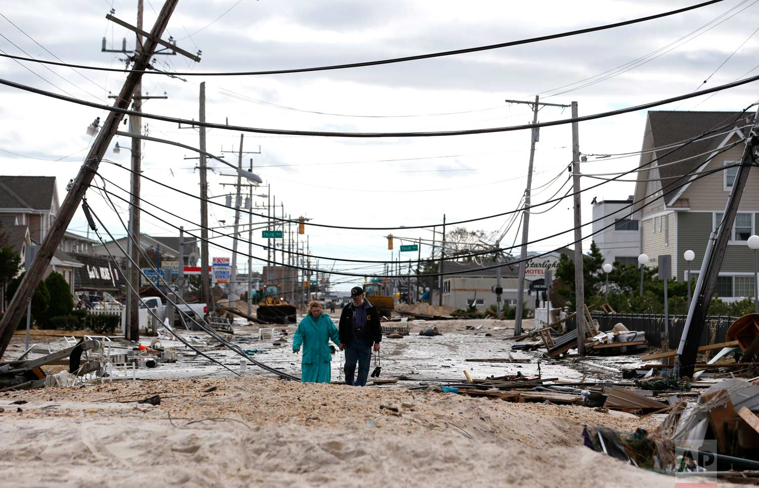Robert Bryce, right, walks with his wife, Marcia Bryce, as destruction from superstorm Sandy is seen on Route 35 in Seaside Heights, N.J., Wednesday, Oct. 31, 2012. Sandy, the storm that made landfall Monday, caused multiple fatalities, halted mass transit and cut power to more than 6 million homes and businesses. (AP Photo/Julio Cortez)