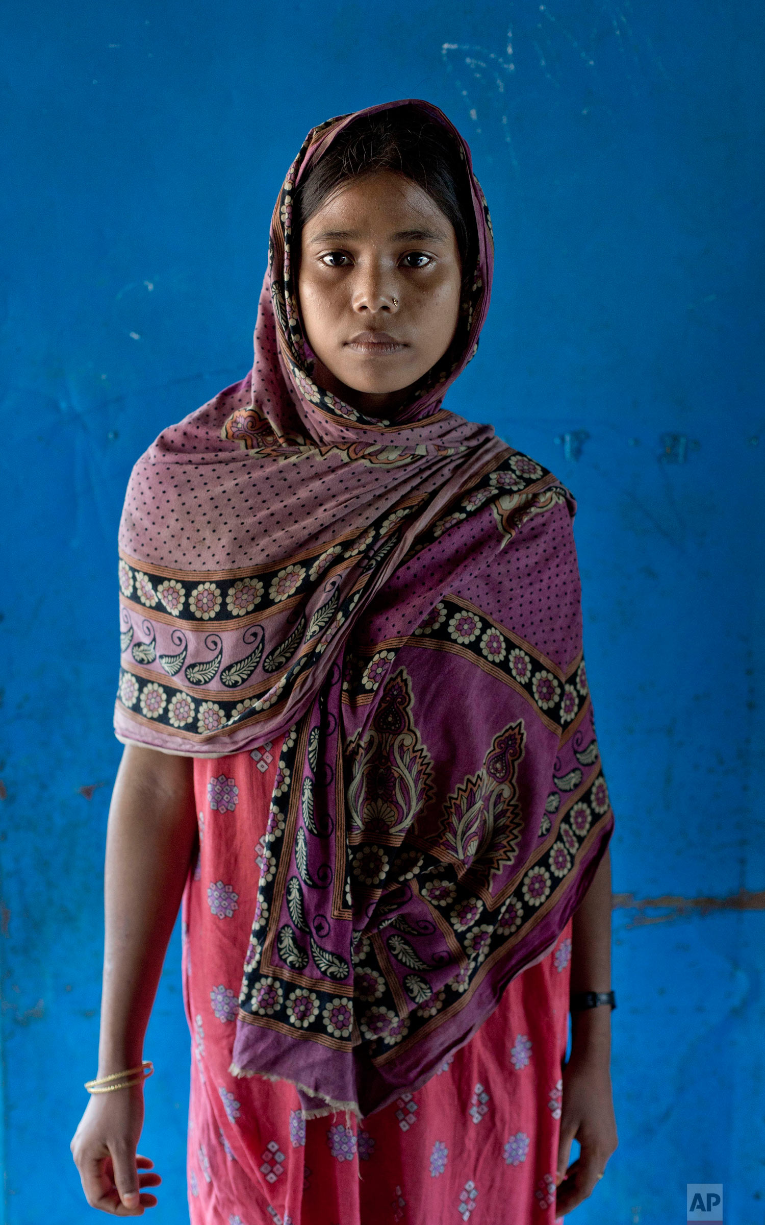 In this Oct. 1, 2017, photo, survivor of a boat capsize Fatima Khatun, from Myanmar's Moidaung Village, stands for a photograph at a transit shelter at Kutupalong camp for newly arrived Rohingya refugees in Bangladesh. Fatima lost her mother and two siblings when the boat they were traveling in, to escape from Myanmar, capsized on Sept. 28. She survived along with her father Lalu Mia and two other siblings. (AP Photo/Gemunu Amarasinghe)