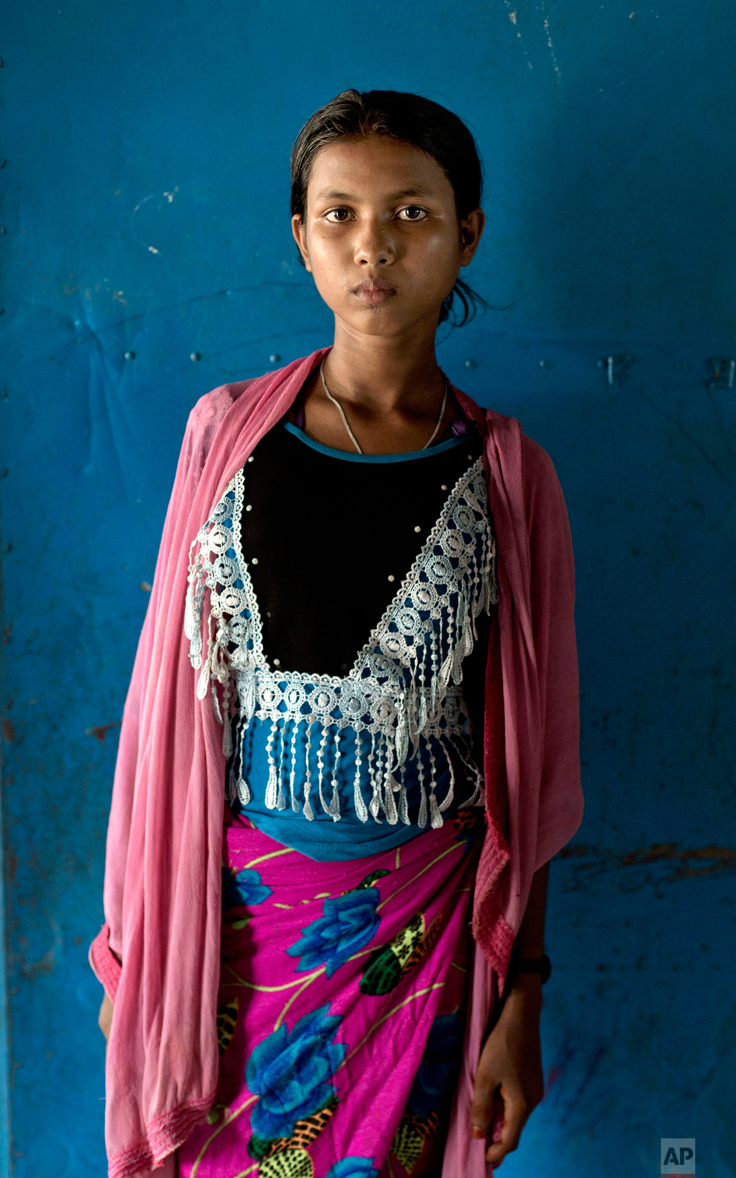 In this Oct. 1, 2017, photo, thirteen-year old survivor of a boat capsize Tosilima, from Myanmar's Moidaung Village, stands for a photograph at a transit shelter at Kutupalong camp for newly arrived Rohingya refugees in Bangladesh. Tosilima's mother and two sisters  drowned when a boat they were traveling in, to make their escape from Myanmar, capsized on Sept. 28. She survived along with her father Mohamed Kasim and three siblings. (AP Photo/Gemunu Amarasinghe)