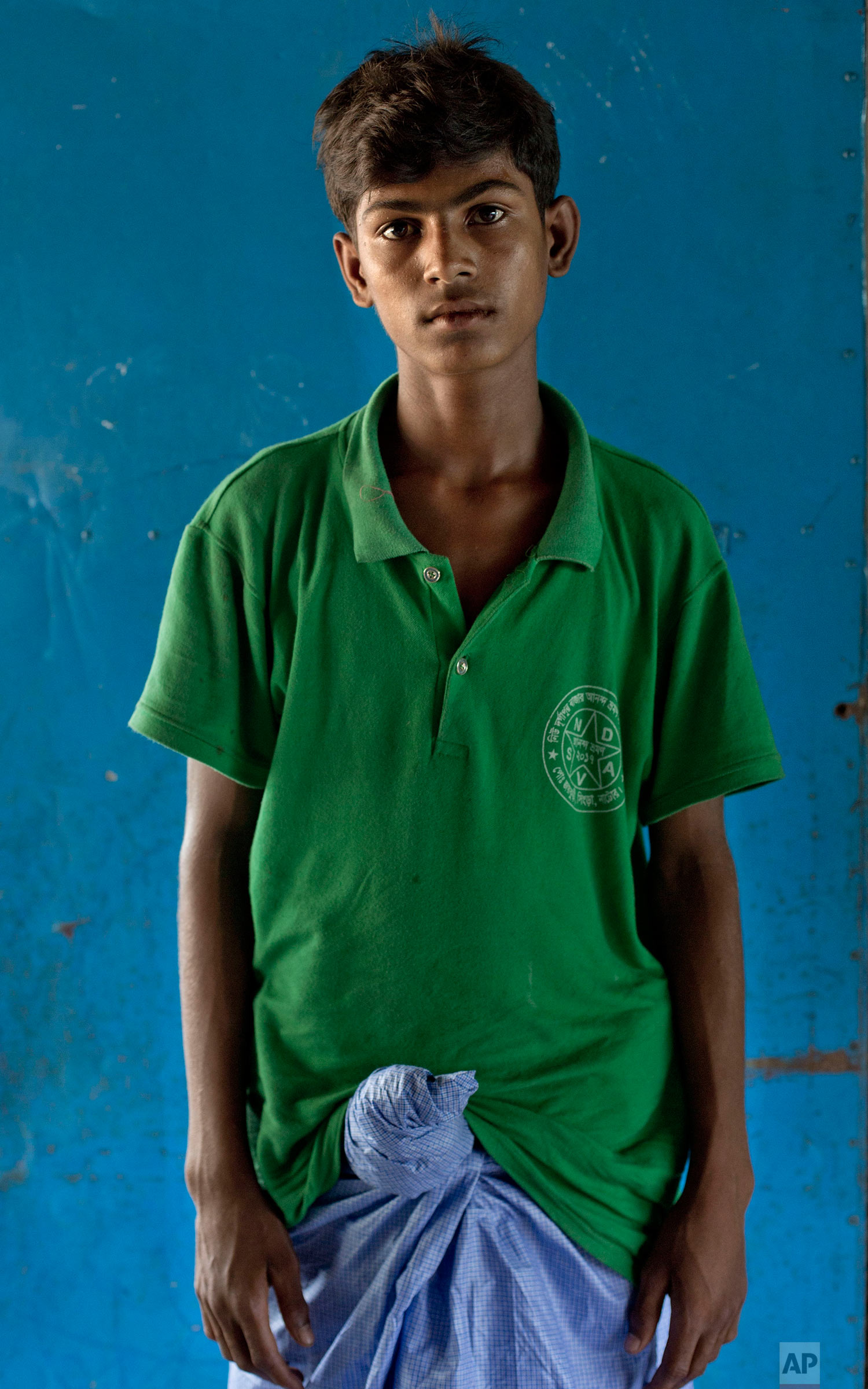 In this Oct. 1, 2017, photo, 16-year-old Abdul Rashid, from Myanmar's Moidaung village, poses for a photograph at a transit shelter at Kutupalong camp for newly arrived Rohingya refugees in Bangladesh. Abdul's mother drowned when the boat she was traveling in along with her four sons capsized on Sept. 29. The brothers said their father was shot and killed by the Myanmar army. (AP Photo/Gemunu Amarasinghe)