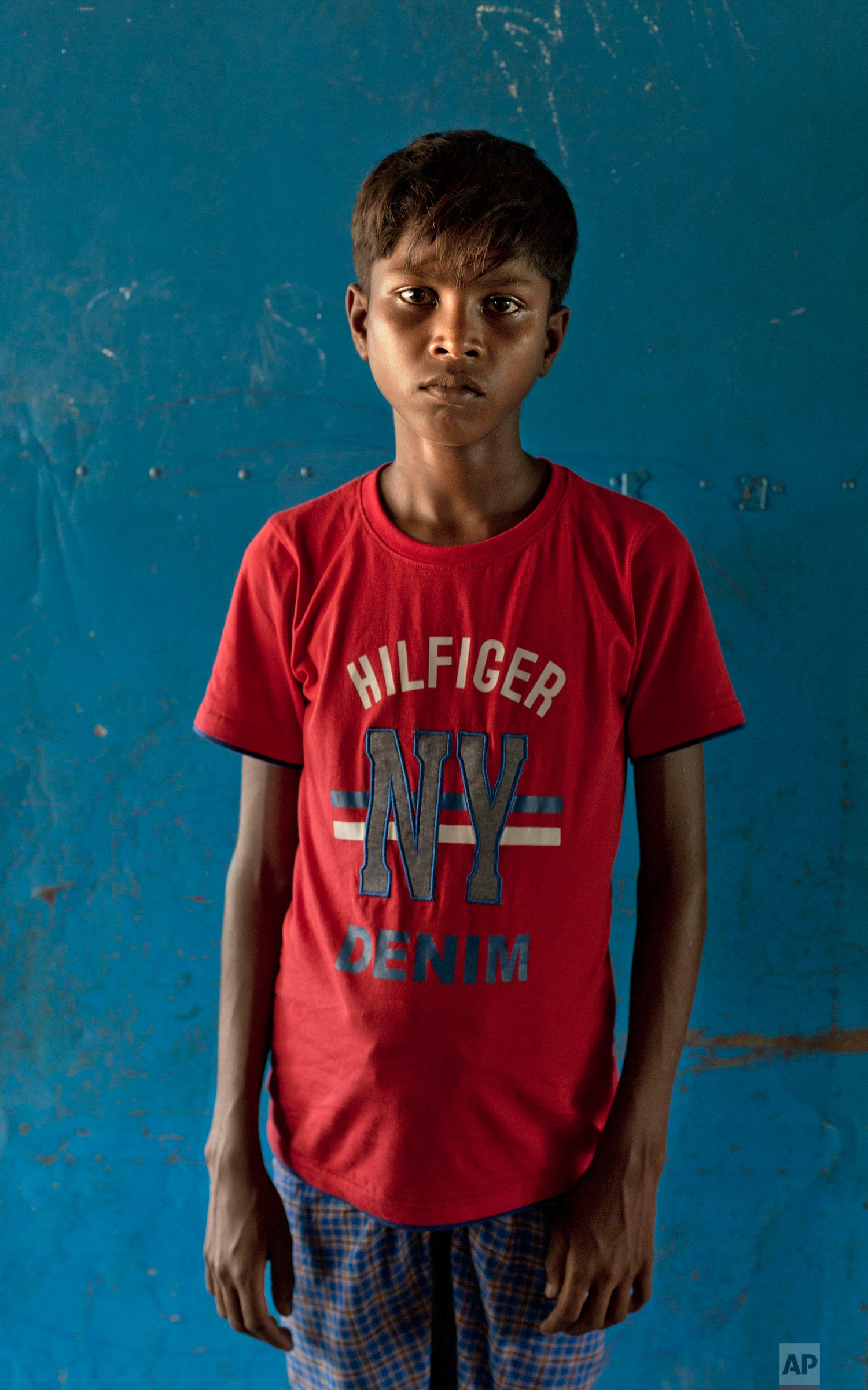 In this Oct. 1, 2017, photo, a Rohingya Muslim boy from Myanmar's Moidaung Village Abdul Gawfar, 13, poses for a photograph inside a transit shelter at Kutupalong camp for newly arrived Rohingya refugees in Bangladesh. His mother drowned when the boat the family was traveling in capsized on Sept. 29. Gophor almost drowned too and was reunited with his brothers after two days of medical treatment. His mother drowned in the accident. The brothers said their father was shot and killed by the Myanmar army. (AP Photo/Gemunu Amarasinghe)