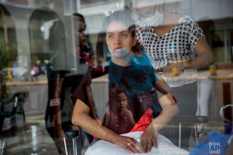 Dayanara Monsalve is seen through a window while waiting for her hairdresser to finish hydrating her hair, in downtown Caracas, Venezuela, Wednesday, Oct. 25, 2017. (AP Photo/Rodrigo Abd)