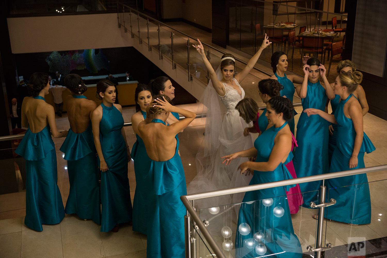 Bride Rhandall Mondelo, 27, center, celebrates after a photo shoot for her weeding in the lobby of an upscale hotel in Caracas, Venezuela, Saturday, Oct. 21, 2017. (AP Photo/Rodrigo Abd)