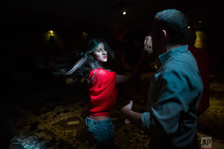 People salsa dance at a club in the financial district of Caracas, Venezuela, Thursday, Oct. 26, 2017. (AP Photo/Rodrigo Abd)