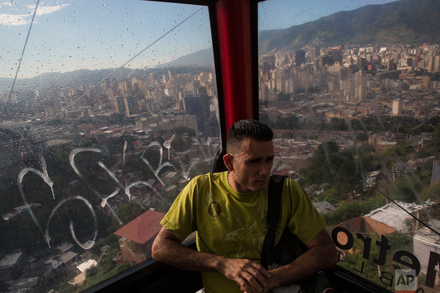 A commuter travels in a cable car over the San Agustin shantytown, in Caracas, Venezuela, Tuesday afternoon, Oct. 24, 2017. (AP Photo/Rodrigo Abd)