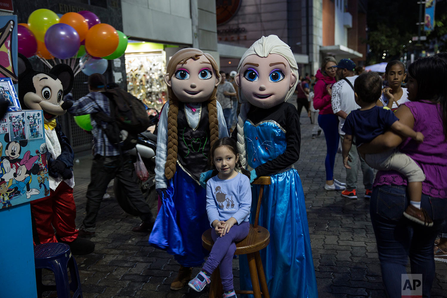 A girl sits next to Disney characters after a street photographer took her photo in downtown Caracas, Venezuela, Saturday, Oct. 21, 2017. (AP Photo/Rodrigo Abd)