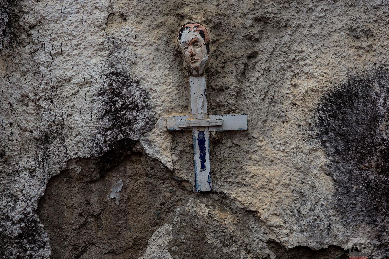 A small mask depicting Venezuela's independence leader Simon Bolivar decorates the top of a cross hanging on a wall along the street in La Vega neighborhood of Caracas, Venezuela, Thursday, Oct. 26, 2017. (AP Photo/Rodrigo Abd)