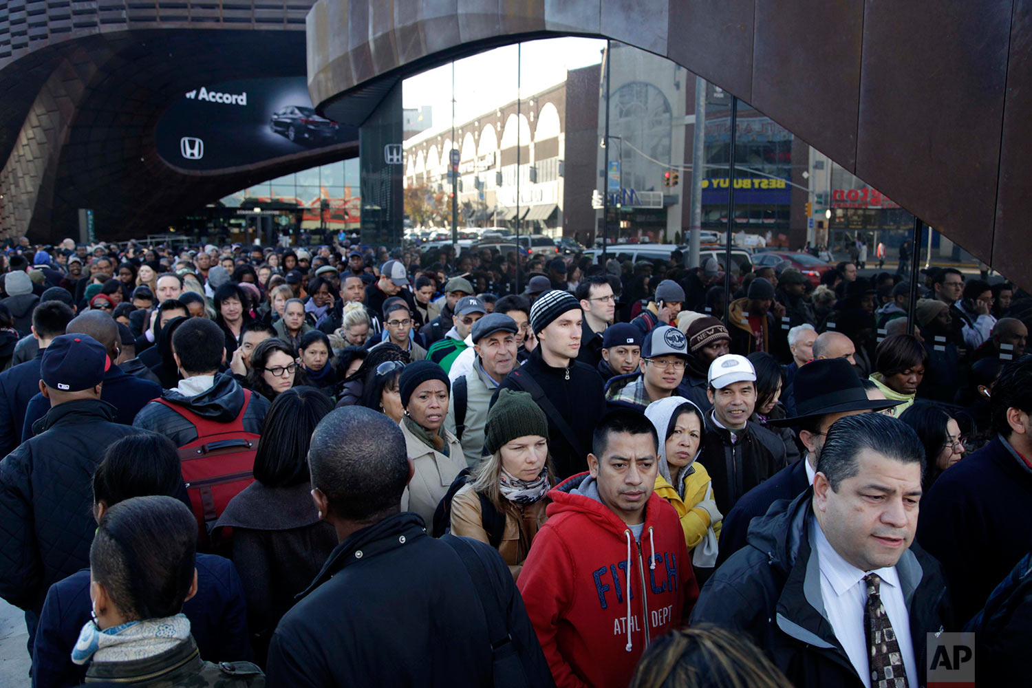 Commuters wait in a line to board buses into Manhattan in front of the Barclays Center in Brooklyn, New York, Thursday, Nov. 1, 2012. The line stretched twice around the arena and commuters reported wait times of one to three hours to get on a bus. (AP Photo/Seth Wenig)
