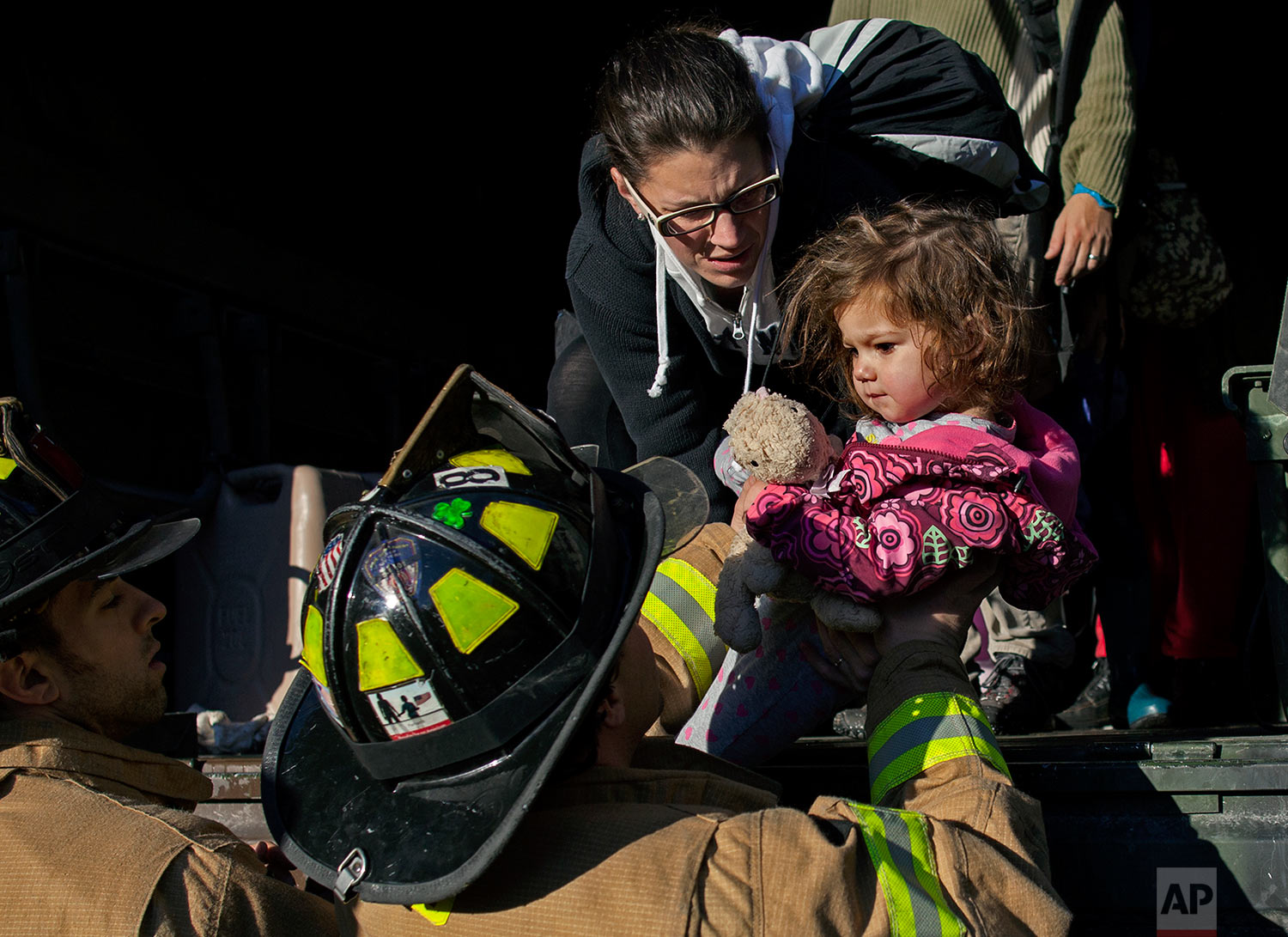 On a National Guard truck, Ali LaPointe, of Hoboken, N.J., hands her daughter Eliza Skye LaPointe, 18-months-old, to Hoboken firefighters, Wednesday, Oct. 31, 2012, in Hoboken, N.J., in the wake of superstorm Sandy. Some residents are being plucked from their homes by large trucks as parts of the city are still covered in standing water. (AP Photo/Craig Ruttle)