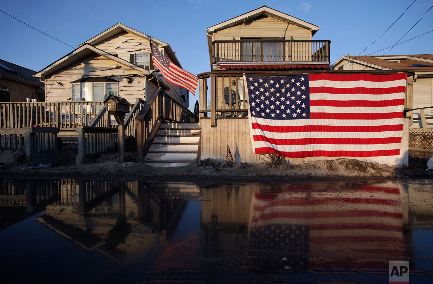 United States flags are displayed on flood-damaged homes in the Breezy Point section of Queens, N.Y., Wednesday, Nov. 28, 2012. (AP Photo/Mark Lennihan)