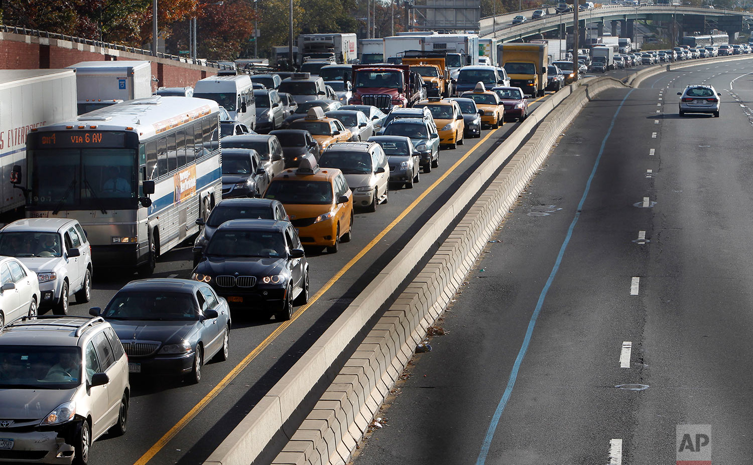 In a photo made through a chain-link fence, traffic is gridlocked on the Long Island Expressway into Manhattan near the turn off for the Queensboro Bridge, Thursday, Nov. 1, 2012, in the Queens borough of New York. New York's subway system rumbled partially back to life Thursday, though the morning commute was plagued by long delays and massive gridlock on the main highways and bridges leading into the city. (AP Photo/Jason DeCrow)