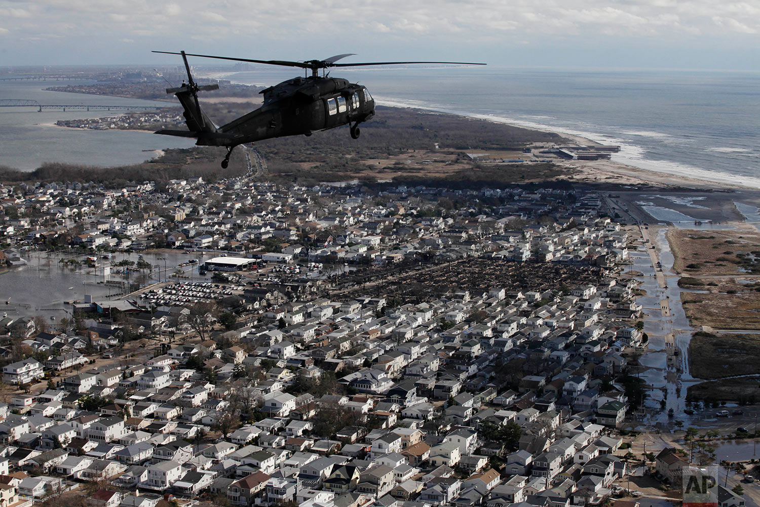 In this Oct. 31, 2012 aerial photo, a New York Air National Guard helicopter with Gov. Andrew Cuomo aboard flies over the ocean side community of Breezy Point in the Queens borough of New York to survey the damage caused by Superstorm Sandy. (AP Photo/Mark Lennihan)