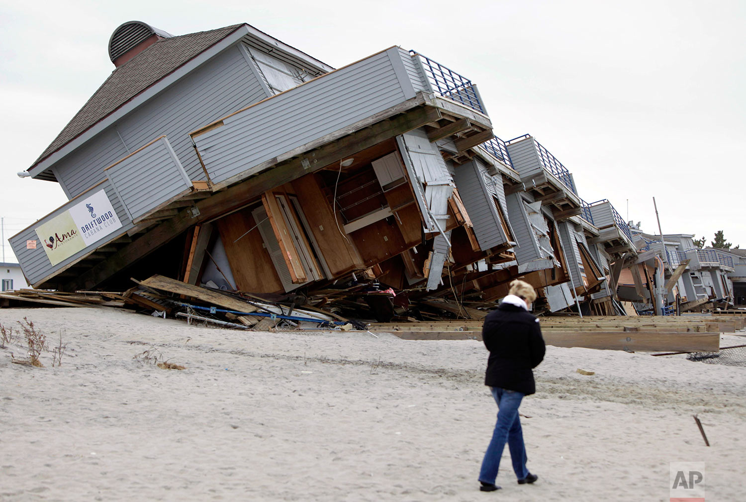 A woman walks past a cabana complex on the beach pulled off its foundations by Superstorm Sandy in Sea Bright, N.J., Monday, Nov. 19, 2012. (AP Photo/Seth Wenig)