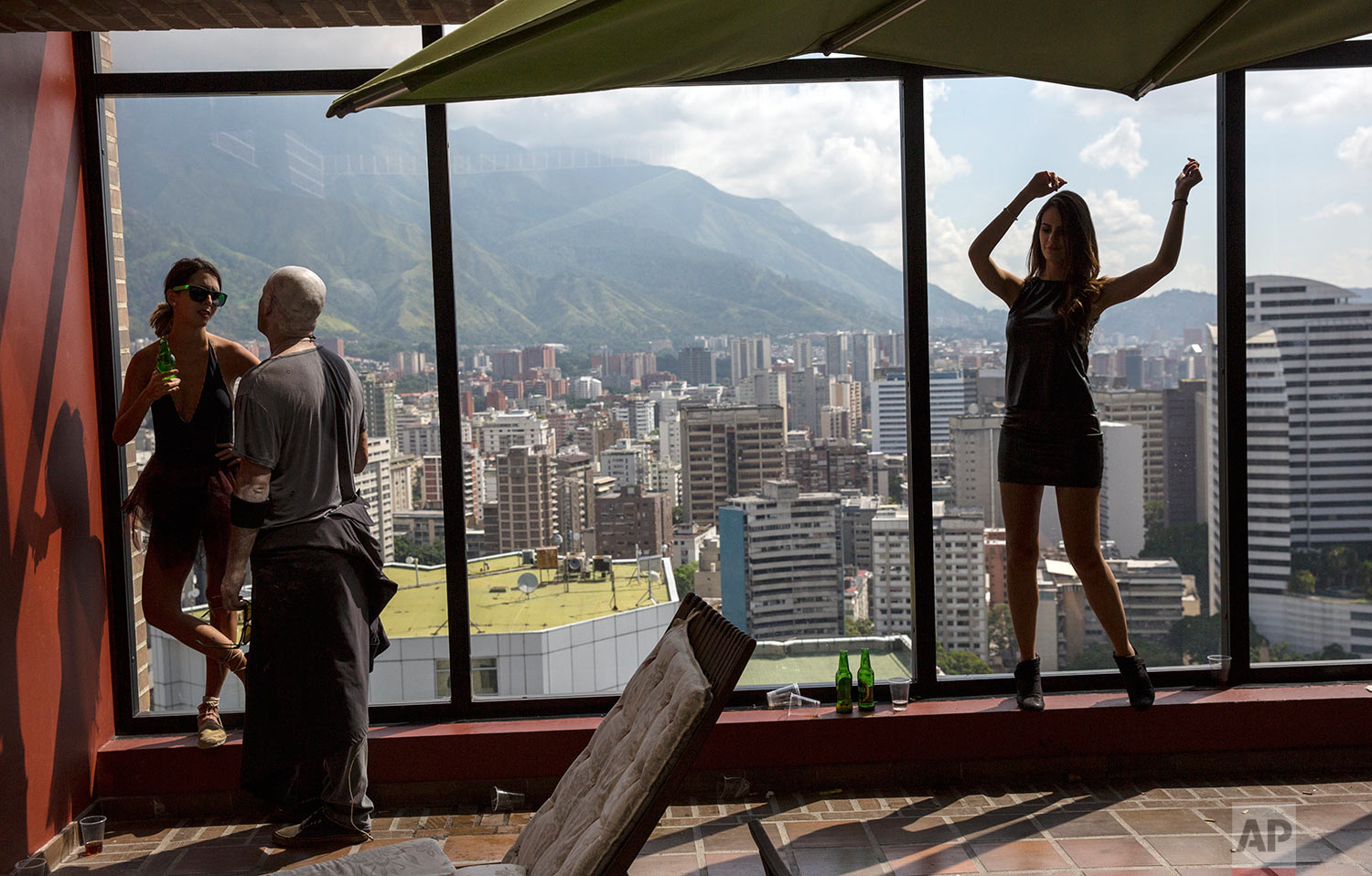 A women dances in the morning, following an all-night party in the presidential suite of an upscale hotel in Caracas, Venezuela, Sunday, Oct. 29, 2017. (AP Photo/Rodrigo Abd)
