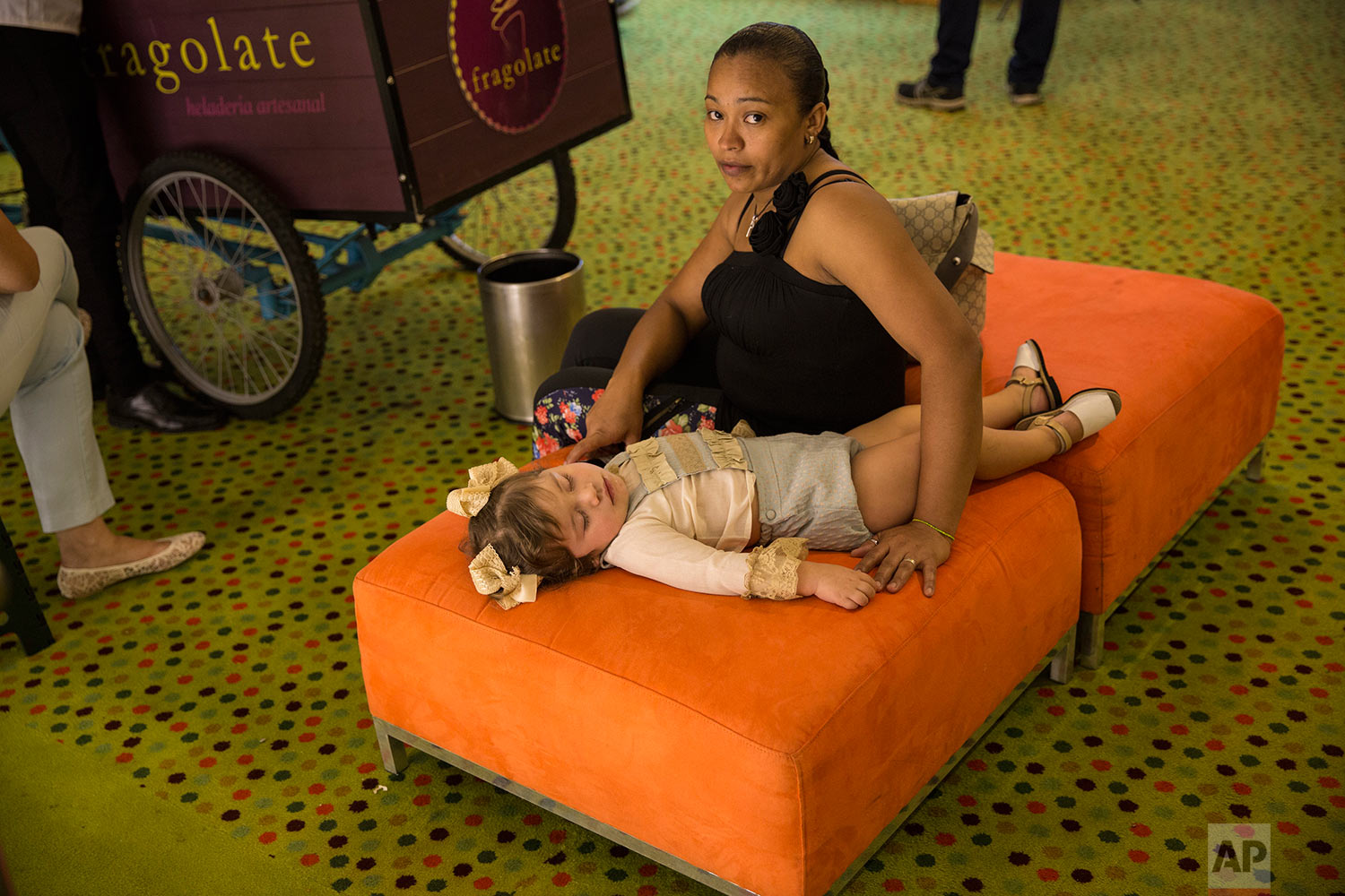 Nanny Luz Mary watches over as two-year-old Gladys sleeps outside a boutique shops exhibition hall inside a upscale hotel in Caracas, Venezuela, Sunday, Oct. 29, 2017. (AP Photo/Rodrigo Abd)